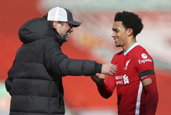 Liverpool's manager Jurgen Klopp greets Trent Alexander-Arnold at the end of the English Premier League soccer match between Liverpool and Aston Villa at Anfield stadium in Liverpool, England, Saturday, April 10, 2021. (Clive Brunskill/Pool via AP)