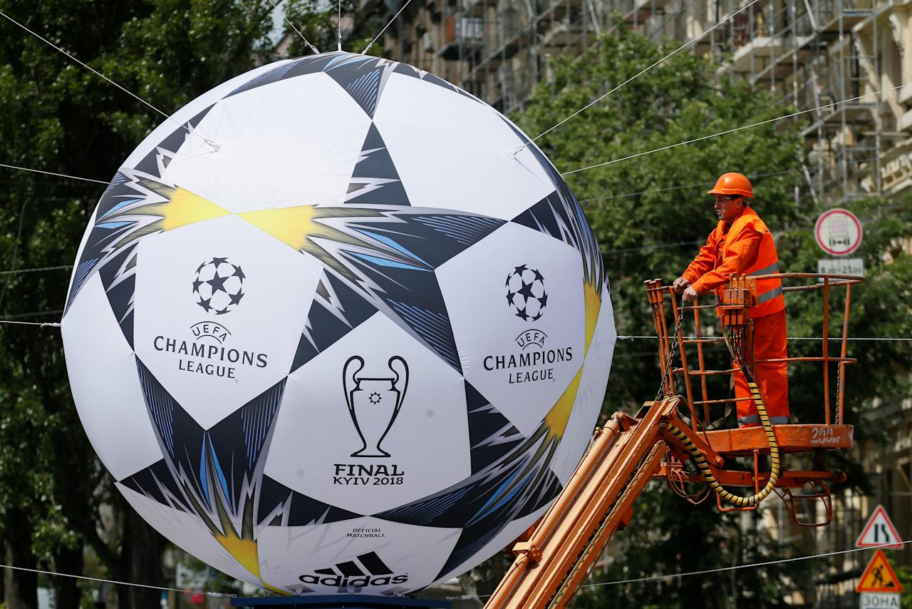 A worker installs a giant model of the official UEFA Champions League final ball in central Kiev, Ukraine May 21, 2018.  REUTERS/Valentyn Ogirenko