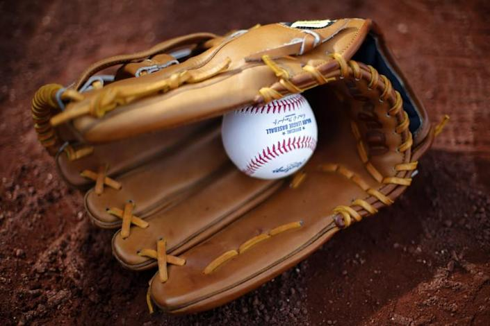 A Wilson baseball glove lies with a baseball in it on the field at PNC Park before a baseball game.