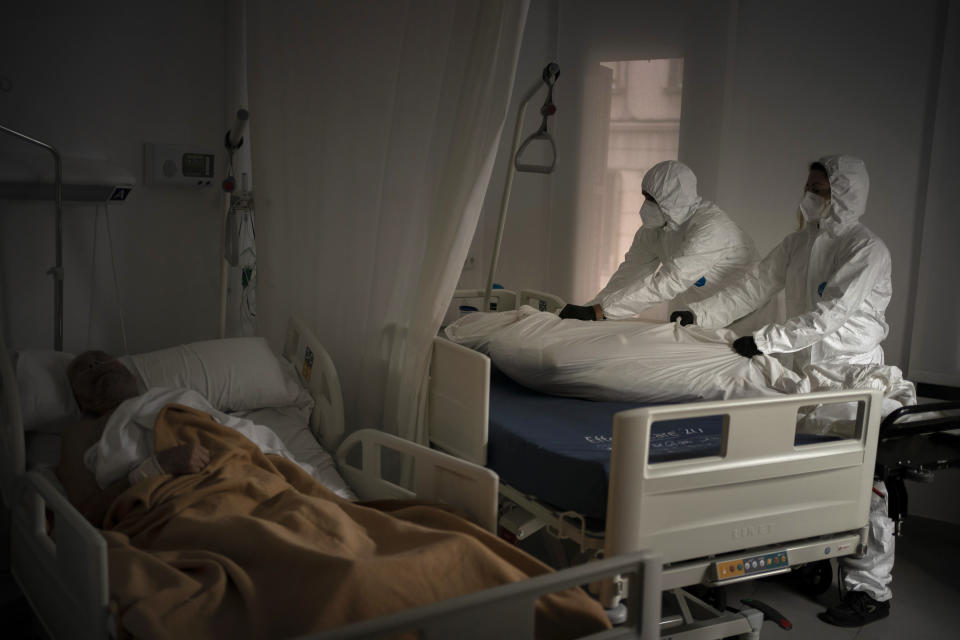 Wearing protective suits against infection, funeral home workers remove the body of an elderly person who died of COVID-19 at a nursing home while another resident sleeps in his bed in Barcelona, Spain Thursday Nov. 5, 2020. (AP Photo/Emilio Morenatti)