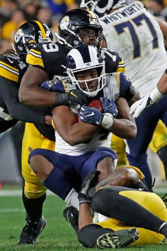 Los Angeles Rams running back Malcolm Brown (34) is tackled by Pittsburgh Steelers nose tackle Javon Hargrave (79) and outside linebacker Bud Dupree, bottom right, during the second half of an NFL football game in Pittsburgh, Sunday, Nov. 10, 2019. (AP Photo/Don Wright)