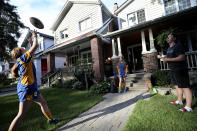 Ruby Wood, left, and her twin sister, Lola, practice rugby with their brother, Ethan, in front of their home in Toronto, Canada, on Monday, July 12, 2021. When Canada recently began immunizing children from 12 years of age, their parents didn't hesitate to get them vaccinated. (AP Photo/Kamran Jebreili)