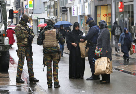 Belgian soldiers and a police officer control the documents of a woman in a shopping street in central Brussels, November 21, 2015. REUTERS/Youssef Boudlal