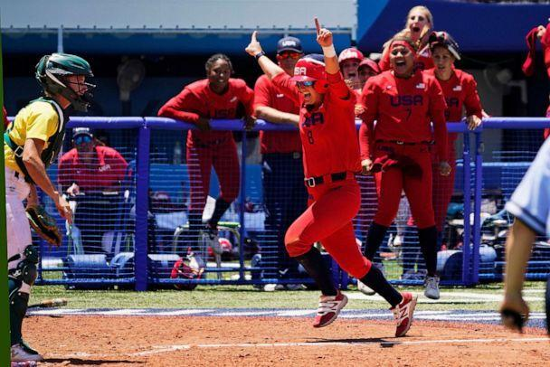 PHOTO: United States' Haylie McCleney scores the game winning run in front of Australia's Belinda White, left, in the eighth inning of a softball game at the 2020 Summer Olympics, Sunday, July 25, 2021, in Yokohama, Japan. (Sue Ogrocki/AP Photo)