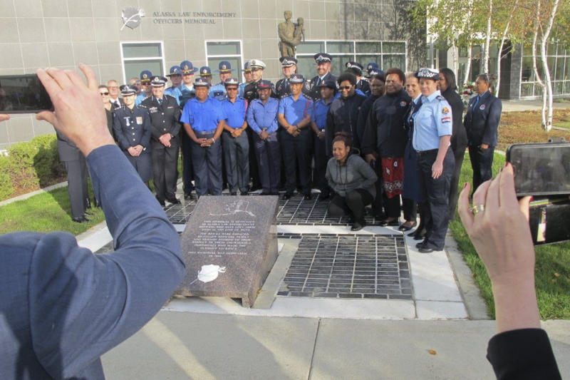 Law enforcement representatives from Australia, New Zealand and Papua New Guinea pose with their Alaska counterparts after a police remembrance ceremony Friday, Sept. 27, 2019, in Anchorage, Alaska. Participants were among delegates attending an international police convention who observed their region's fallen officers in the quickly planned ceremony with their Alaska counterparts. (AP Photo/Rachel D'Oro)