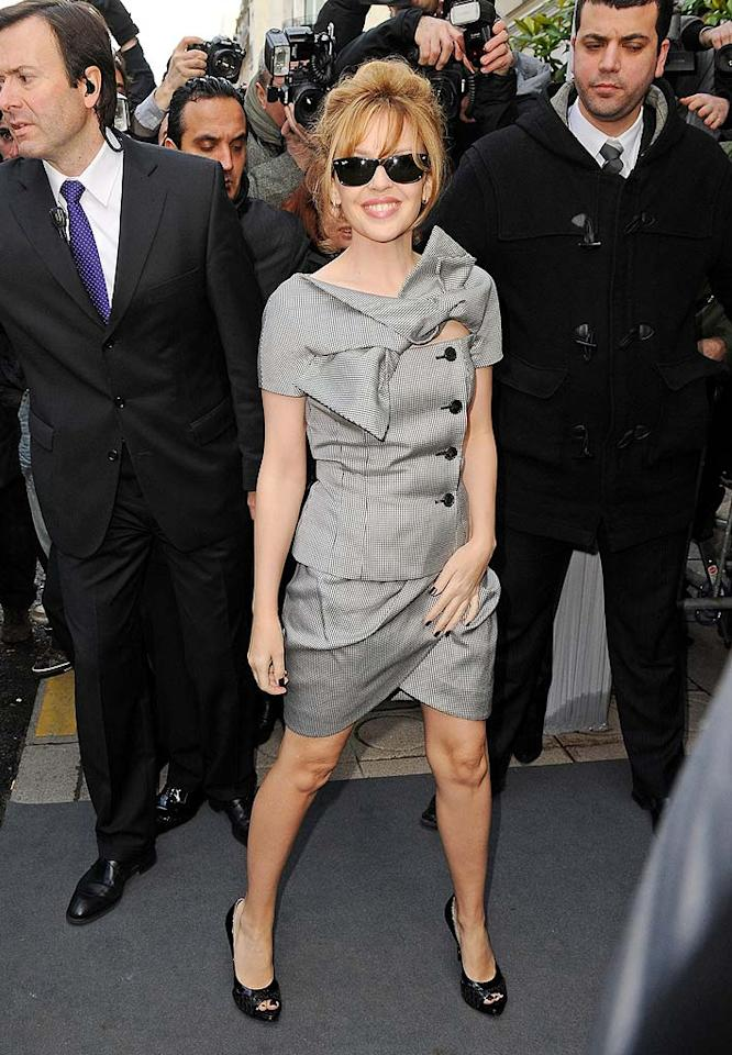 """Pint-sized pop princess, Kylie Minogue, wearing a chic grey skirt suit from the Christian Dior Spring 2010 ready-to-wear collection, posed with some serious-looking bodyguards outside the Dior show. Dominique Charriau/<a href=""""http://www.wireimage.com"""" target=""""new"""">WireImage.com</a> - January 25, 2010"""