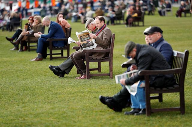Horse Racing - Cheltenham Festival - Cheltenham Racecourse, Cheltenham, Britain - March 13, 2018 Racegoers sit on benches Action Images via Reuters/Andrew Boyers