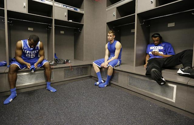 Kentucky guard Dominique Hawkins, left, reacts with teammates in the locker room after their 60-54 loss to Connecticut in the NCAA Final Four tournament college basketball championship game Monday, April 7, 2014, in Arlington, Texas. (AP Photo/Eric Gay)