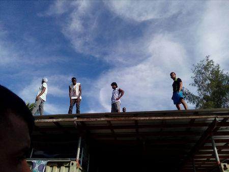 Asylum seekers occupying the closed Australian-run immigration detention centre on Papua New Guinea's Manus Island climb on top of buildings at the centre to avoid police
