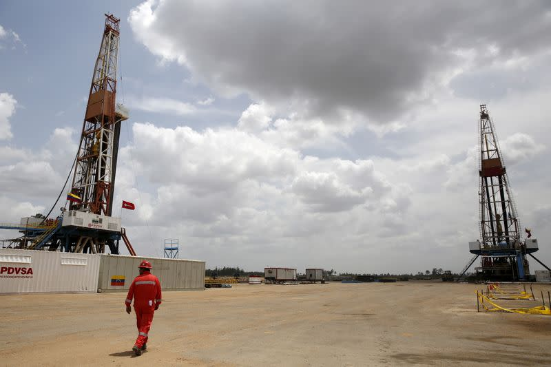 FILE PHOTO: An oilfield worker walks next to drilling rigs at an oil well operated by Venezuela's state oil company PDVSA, in the oil rich Orinoco belt, near Morichal at the state of Monagas