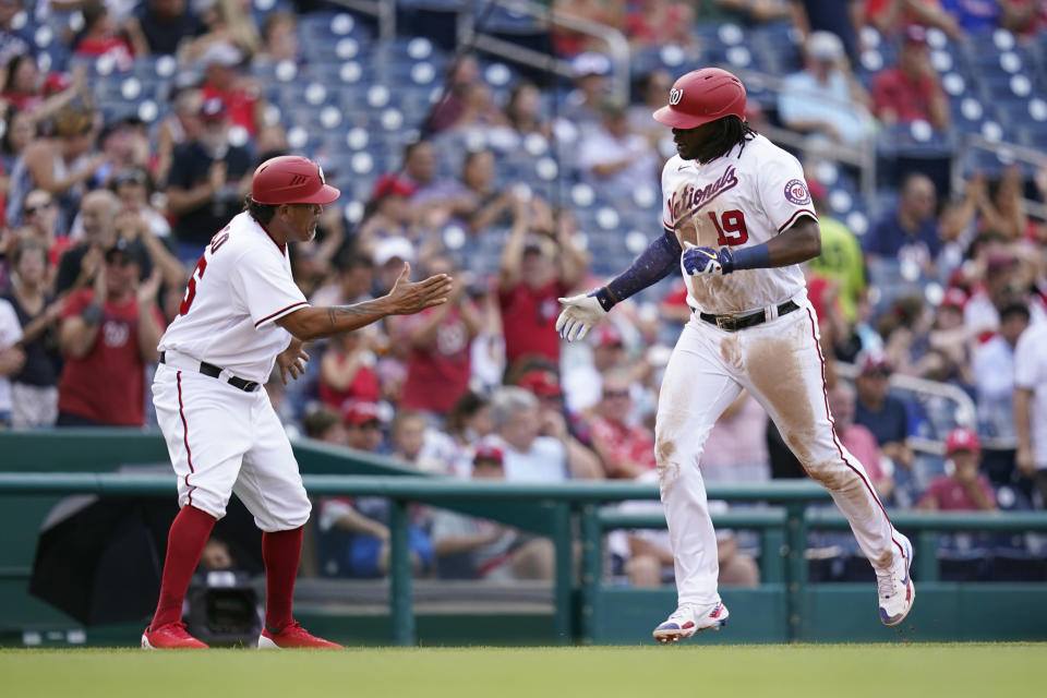 Washington Nationals' Josh Bell rounds the bases past interim third base coach Henry Blanco after hitting a three-run home run in the fifth inning of a baseball game against the Philadelphia Phillies, Thursday, Aug. 5, 2021, in Washington. (AP Photo/Patrick Semansky)