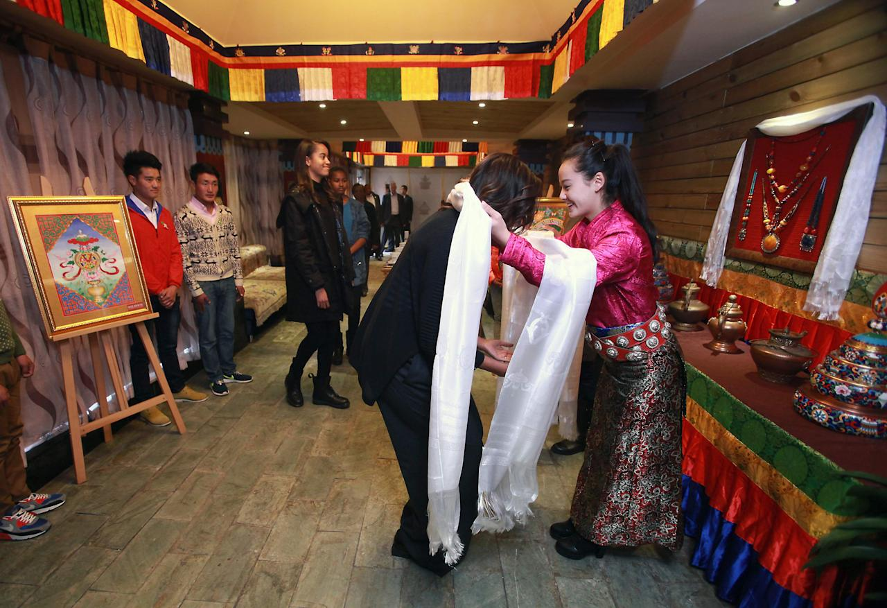 U.S. first lady Michelle Obama (2nd R) receives a traditional prayer scarf from an attendant while daughters Malia (L) and Sasha wait their turn, upon arrival for lunch at the Zangxiang Teahouse in Chengdu, the capital of Sichuan Province, March 26, 2014. REUTERS/Stephen Shaver/Pool (CHINA - Tags: POLITICS RELIGION FOOD SOCIETY)