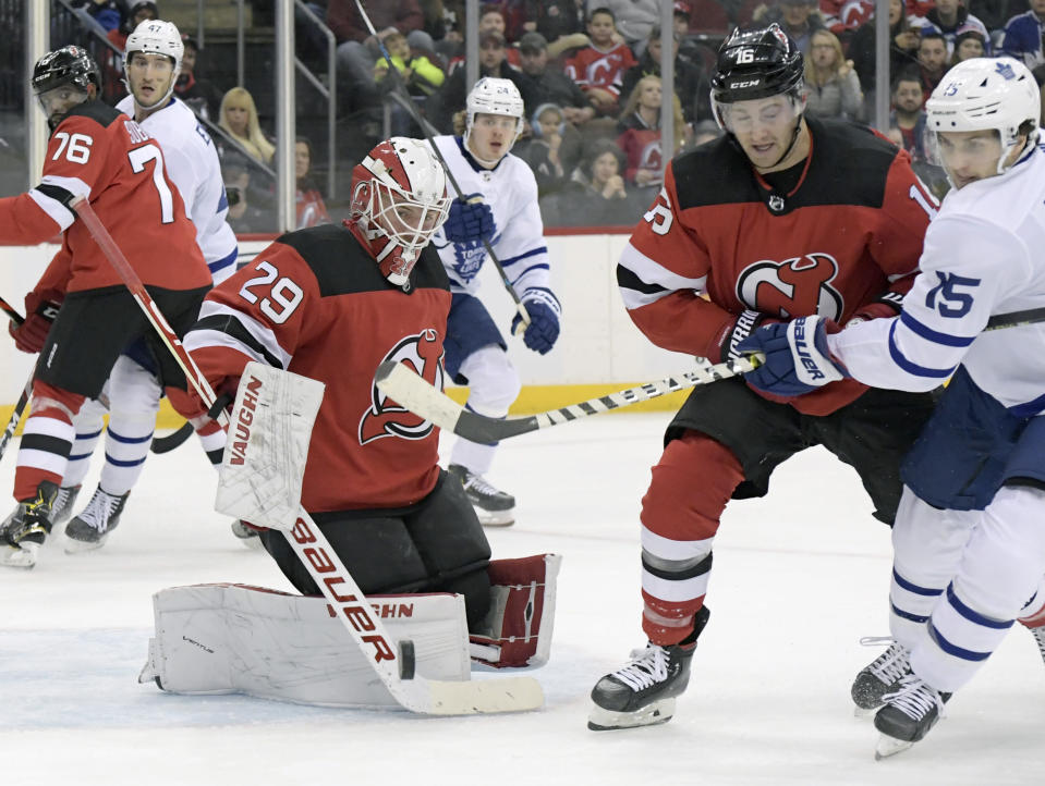 New Jersey Devils goaltender Mackenzie Blackwood (29) deflects the puck as Devils center Kevin Rooney (16) and Toronto Maple Leafs center Alexander Kerfoot (15) chase after the puck during the first period of an NHL hockey game Friday, Dec. 27, 2019, in Newark, N.J. (AP Photo/Bill Kostroun)