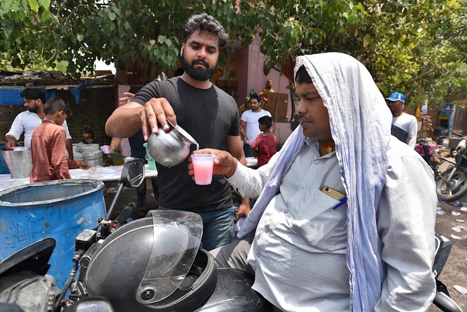 NEW DELHI, INDIA - JUNE 9: Local residents distribute flavoured water as a goodwill gesture to passersby on a summer day, at Chattarpur, on June 9, 2019 in New Delhi, India. The national capital reeled under scorching heat Saturday, with high humidity adding to the discomfort of the residents. Delhi is expected to record a high of 44 and a low of 29 degrees Celsius, a MeT official said. (Photo by Burhaan Kinu/Hindustan Times via Getty Images)