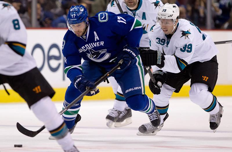 Vancouver Canucks' Ryan Kesler, left, skates through center ice with the puck as San Jose Sharks' Logan Couture gives chase during the first period of an NHL hockey game, Thursday, Oct. 10, 2013 in Vancouver, British Columbia. (AP Photo/The Canadian Press, Darryl Dyck)