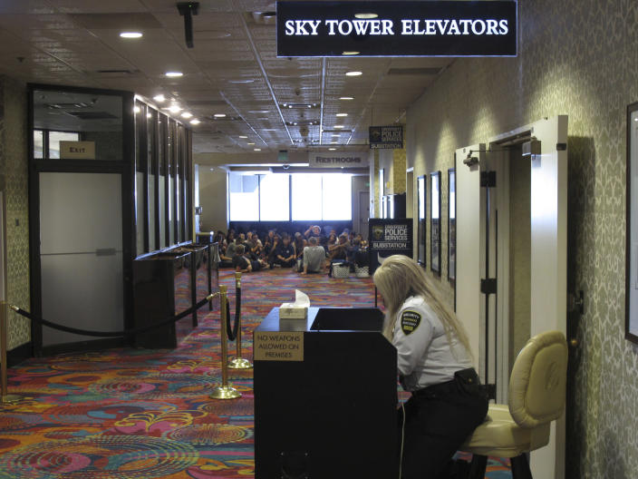 A security guard sits at a check point next to the elevators while University of Nevada resident assistants sit in the background on Aug. 19, 2019 during a training session at the Circus Circus casino hotel tower that's been converted into a residence hall. Renamed Wolf Pack Tower, it will house about 1,300 students this school year after a gas explosion in July shut down two major dorms on the main campus a half-mile away. (AP Photo/Scott Sonner)
