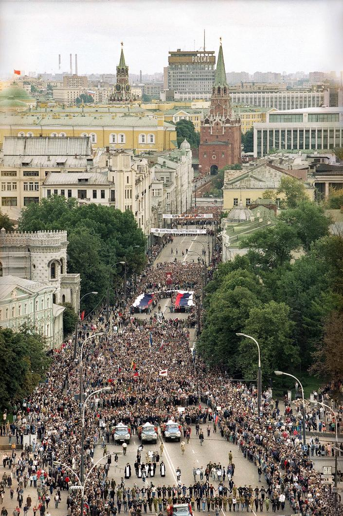 FILE - In this Saturday, Aug. 24, 1991 file photo, thousands of Muscovites carry a huge Russian national flag as they walk with the coffins of three victims of the failed Kremlin coup in Moscow, Russia. When a group of top Communist officials ousted Soviet leader Mikhail Gorbachev 30 years ago and flooded Moscow with tanks, the world held its breath, fearing a rollback on liberal reforms and a return to the Cold War confrontation. But the August 1991 coup collapsed in just three days, precipitating the breakup of the Soviet Union that plotters said they were trying to prevent.(AP Photo/Boris Yurchenko, File)