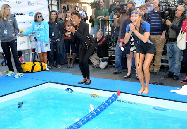 "IMAGE DISTRIBUTED FOR P&G - GMA anchors Robin Roberts, left, and Lara Spencer pretend to join long-distance swimmer Diana Nyad before the start of her 48-hour continuous ""Swim for Relief"" to support Hurricane Sandy recovery efforts, Tuesday, Oct. 8, 2013, in New York's Herald Square. The swim is raising funds for AmeriCares, a non-profit relief organization, with P&G brands such as Duracell, Tide and Secret underwriting the production costs to maximize the funds donated. (Photo by Diane Bondareff/Invision for P&G/AP Images)"