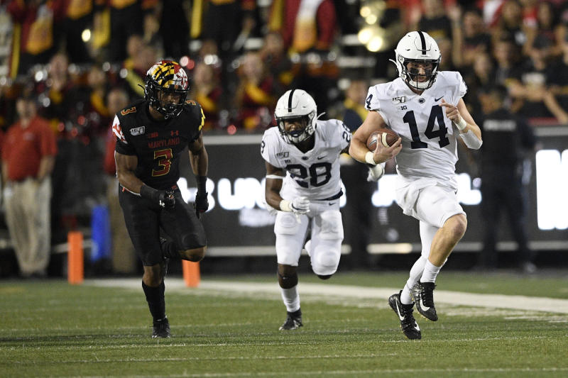 Penn State quarterback Sean Clifford (14) scrambles with the ball against Maryland defensive back Nick Cross (3) during the first half of an NCAA college football game, Friday, Sept. 27, 2019, in College Park, Md. Also seen is Penn State running back Devyn Ford (28). (AP Photo/Nick Wass)