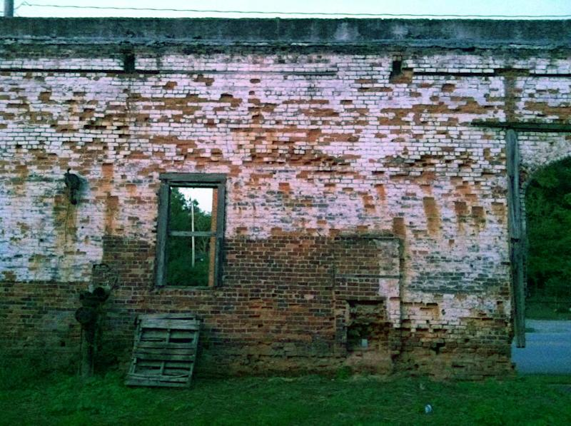 """This Oct. 1, 2013 photo shows the brick wall from an old building in Grantville, Ga., that was used to film a scene in the AMC TV drama """"The Walking Dead."""" Tourists come to the west Georgia town to see the wall and other nearby buildings where scenes from the show were filmed. (AP Photo/Jeff Martin)"""