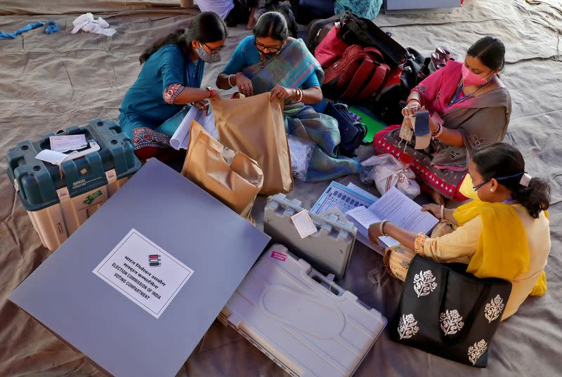 Polling officials check election materials after collecting them from a distribution centre, in Purulia