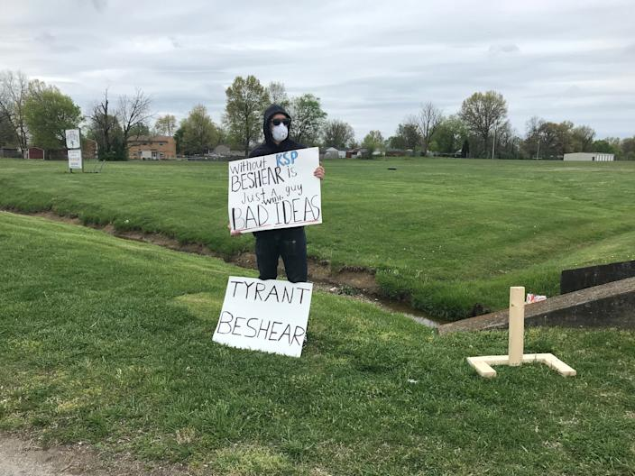 A masked protester criticizes Kentucky Gov. Andy Beshear for directing troopers to take down license plate numbers of people attending in-person Easter service at Maryville Baptist Church in Hillview, Kentucky.