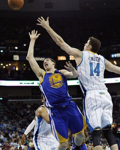 Golden State Warriors guard Klay Thompson (11) drives to the basket past New Orleans Hornets power forward Jason Smith (14) in the first half of an NBA basketball game in New Orleans, Wednesday, March 21, 2012. (AP Photo/Gerald Herbert)