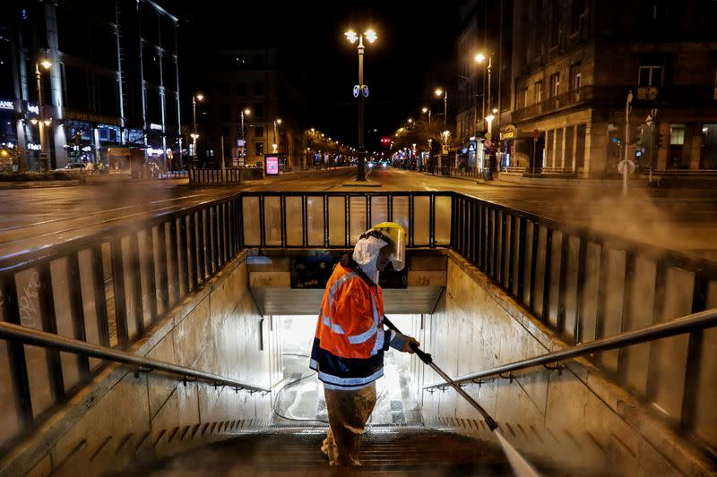 FILE PHOTO: A worker wearing protective suit cleans and disinfects a flight of stairs of an underpass to prevent the spread of coronavirus disease (COVID-19), in downtown Budapest
