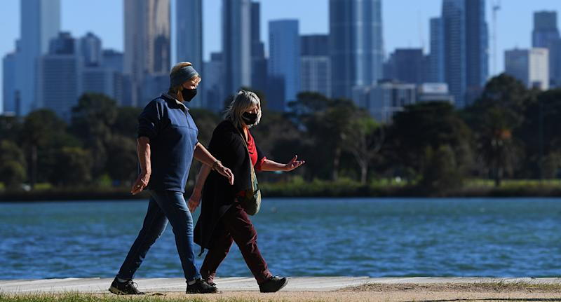 People wearing facemasks are seen exercising along Albert Park Lake in Melbourne.