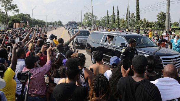 PHOTO: Mourners in procession vehicles pass people in the street viewing the George Floyd funeral procession moments before entering Houston Memorial Gardens Cemetery for Floyd's burial, June 9, 2020, in Pearland, Texas. (Mario Tama/Getty Images)