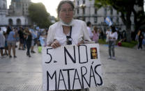 """An activist against abortion holds a sign that reads in Spanish """"Thou Shalt not kill"""" as she protests against the decriminalization of abortion, one day before lawmakers will debate its legalization, at Plaza de Mayo in Buenos Aires, Argentina, Monday, Dec. 28, 2020. (AP Photo/Victor R. Caivano)"""