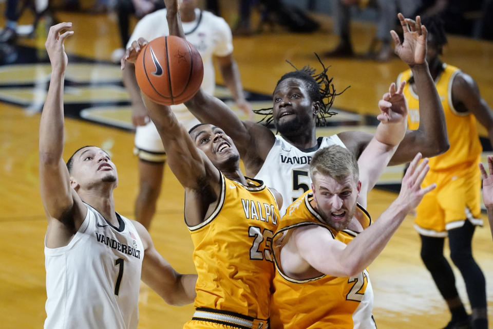 Valparaiso guard Nick Robinson (25) grabs a rebound between Vanderbilt's Dylan Disu (1) and Ejike Obinna (50) in the first half of an NCAA college basketball game Friday, Nov. 27, 2020, in Nashville, Tenn. (AP Photo/Mark Humphrey)