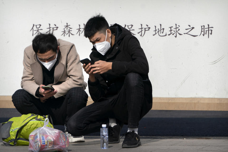 Travelers wearing face masks to protect against the spread of the coronavirus use their smartphones as they wait outside the Beijing Railway Station in Beijing, Wednesday, Feb. 10, 2021. China's internet watchdog is cracking down further on online speech, issuing a new requirement that bloggers and influencers have a government-approved credential before they can publish on certain topics. (AP Photo/Mark Schiefelbein)