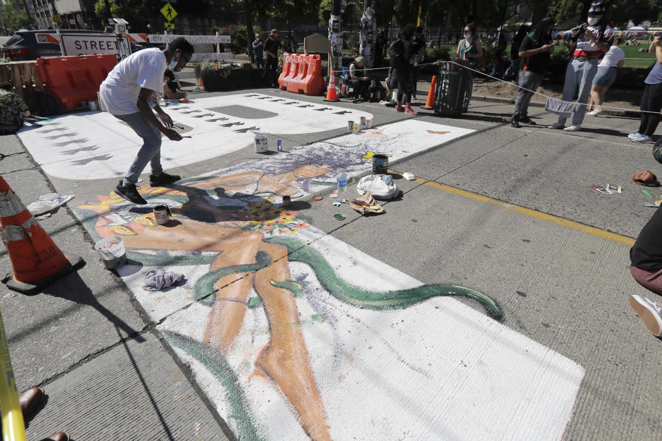 """An artist paints one of the large letters that read """"Black Lives Matter"""" on a street near Cal Anderson Park, Thursday, June 11, 2020, inside what is being called the """"Capitol Hill Autonomous Zone"""" in Seattle. Following days of violent confrontations with protesters, police in Seattle have largely withdrawn from the neighborhood. (AP Photo/Ted S. Warren)"""