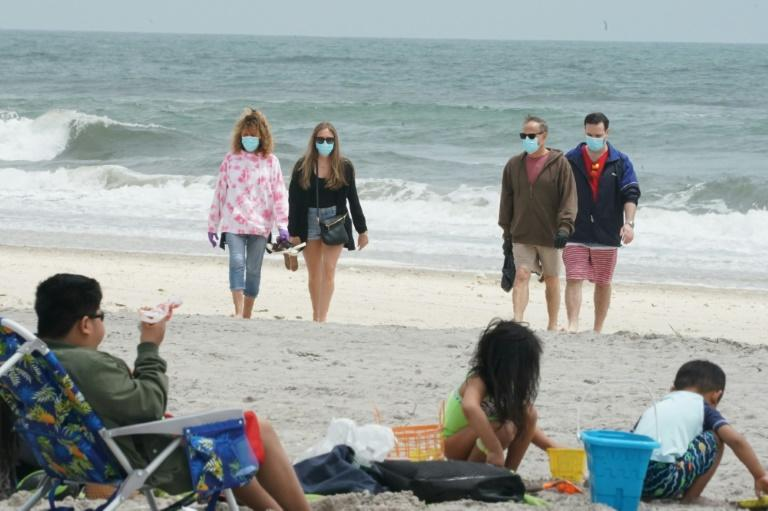 People wear masks as they walk along the shore at Jones Beach on May 24, 2020 on Long Island, New York