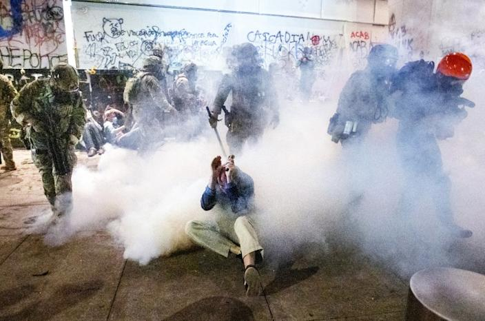 "Federal officers use chemical irritants and crowd control munitions to disperse protesters Wednesday outside the Mark O. Hatfield United States Courthouse in Portland, Ore. <span class=""copyright"">(Noah Berger / Associated Press )</span>"