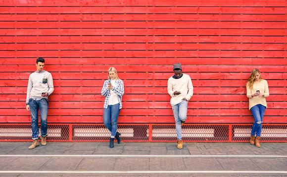Four young people using their smartphones standing against a red wall.