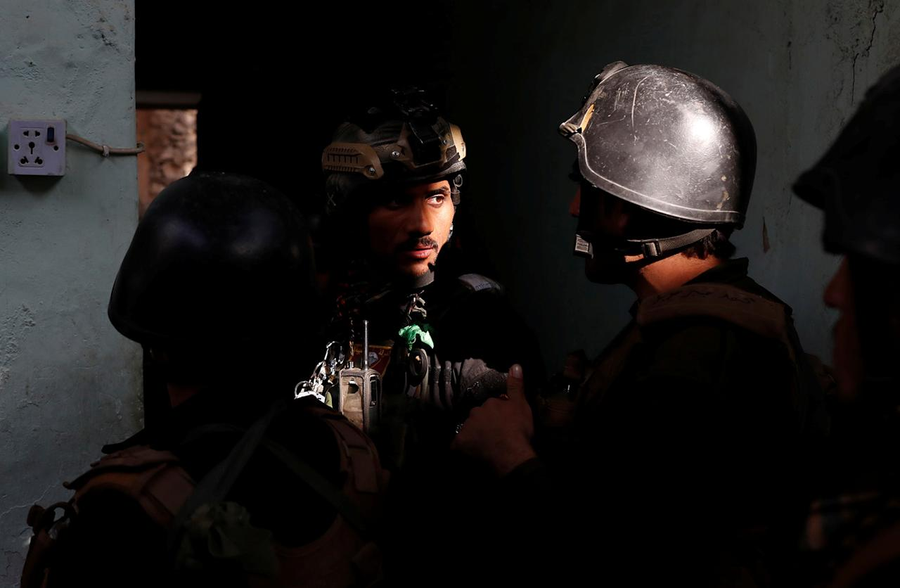 <p>Iraqi special forces soldiers talk to each other as they prepare for attack Islamic State fighters in Mosul, Iraq, Feb. 28, 2017. (Goran Tomasevic/Reuters) </p>