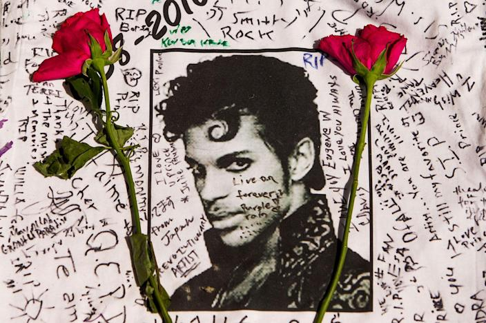 <p>APR. 22, 2016 — Flowers lie on a T-shirt signed by fans of singer Prince at a makeshift memorial place created outside the Apollo Theater in New York. The pop star died at the age of 57. (Andres Kudacki/AP) </p>