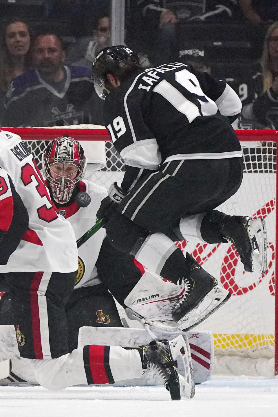 Los Angeles Kings left wing Alex Iafallo, right, jumps out of the way of the puck as Ottawa Senators goaltender Craig Anderson makes a save during the first period of an NHL hockey game Wednesday, March 11, 2020, in Los Angeles. (AP Photo/Mark J. Terrill)