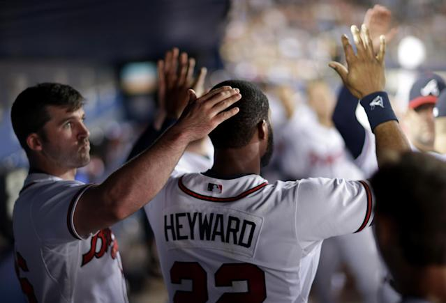 Atlanta Braves' Dan Uggla, left, pats the head of teammate Jason Heyward after Heyward made a diving catch to get out Milwaukee Brewers' Yuniesky Betancourt in the sixth inning of a baseball game, Monday, Sept. 23, 2013, in Atlanta. (AP Photo/David Goldman)