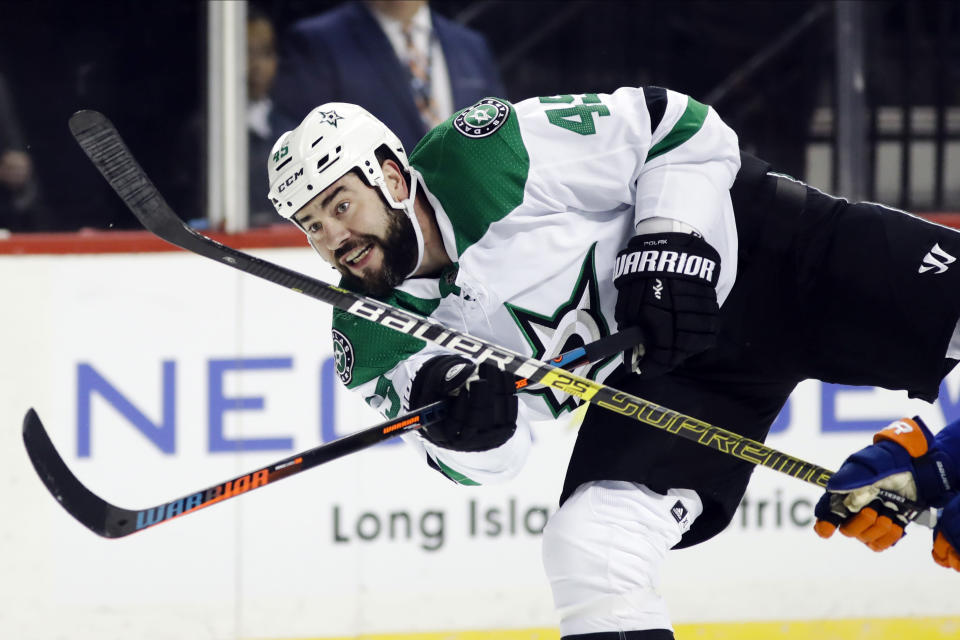 FILE - In this Feb. 4, 2020, file photo, Dallas Stars' Roman Polak (45) shoots on goal during the first period of an NHL hockey game against the New York Islanders in New York. Edmontons Mike Green and Vancouvers Sven Baertschi are opting out. Polak is not reporting for now. And Tampa Bay captain Steven Stamkos is not reporting at full strength. Green and Baertschi joined Calgary defender Travis Hamonic in choosing not to participating in the resumption of the NHL season. Polak is not on the Stars roster for the start of training camp, and a team spokesman said the 34-year-old will not be attending at this time. (AP Photo/Frank Franklin II, File)