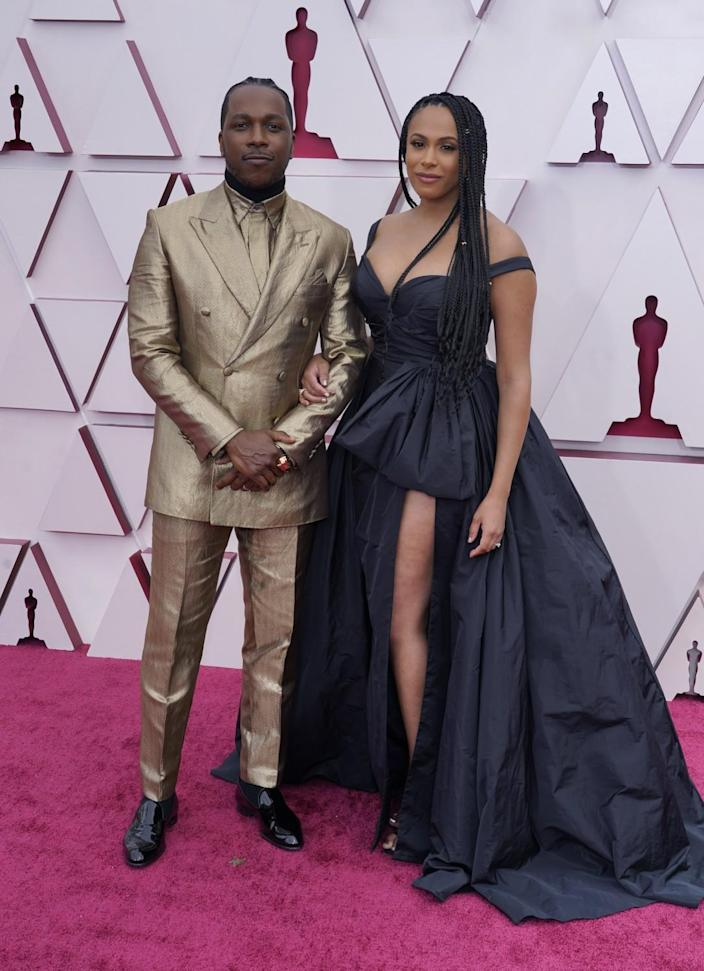 Leslie Odom Jr. in a gold suit and Nicolette Robinson in a dark low-cut dress with one leg showing.