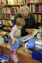 Jaromir Vytopil reads a book to a child at his bookstore in Pelhrimov, Czech Republic, Saturday, May 29, 2010. Some 25,000 have been killed by COVID-19 in the hard-hit Czech Republic. Jaromir Vytopil was one of them. His everyday presence in the small Czech town of Pelhrimov was something everybody took for granted for seven decades as he had served the generations of readers. The longest serving Czech bookseller, passed away on Nov 9. 2020, at age of 83. (AP Photo/Jan Vytopil)