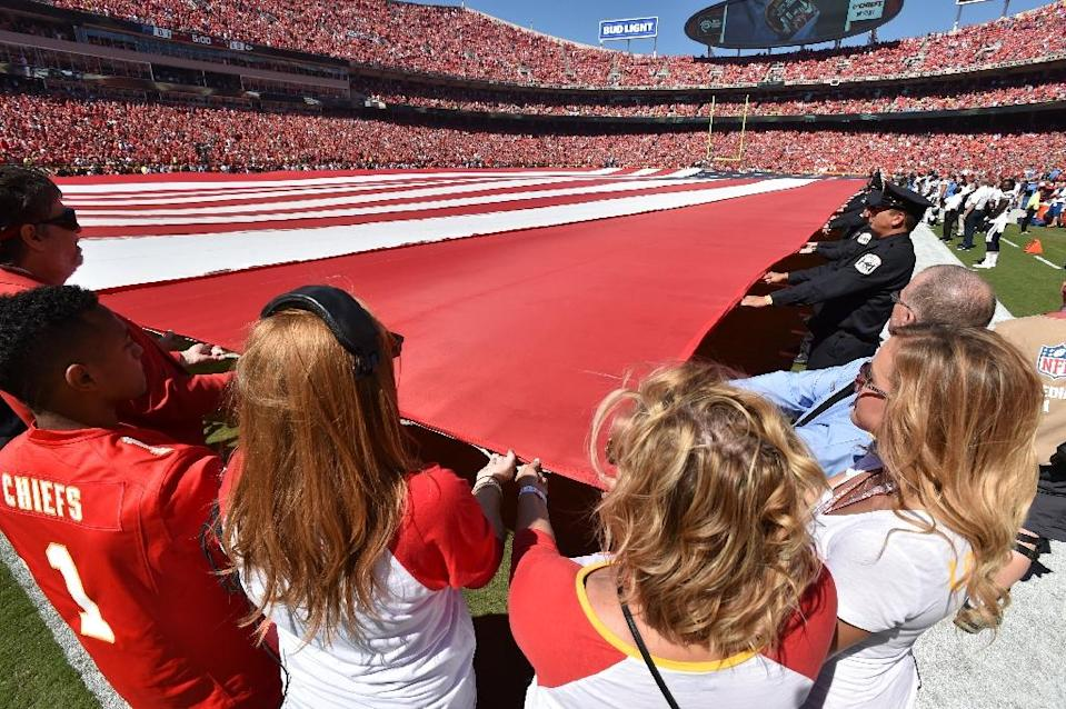 Kansas City Chiefs staff and several members of local law enforcement hold the field length American Flag during the national anthem at Arrowhead Stadium on September 11, 2016 in Kansas City, Missouri (AFP Photo/Peter G Aiken)