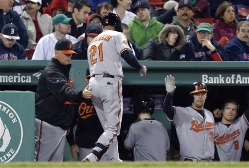 Baltimore Orioles manager Buck Showalter, left, pats Nick Markakis (21) after Marakis' solo home run in the fourth inning of a baseball game against the Boston Red Sox in Boston, Wednesday, April 10, 2013. (AP Photo/Michael Dwyer)