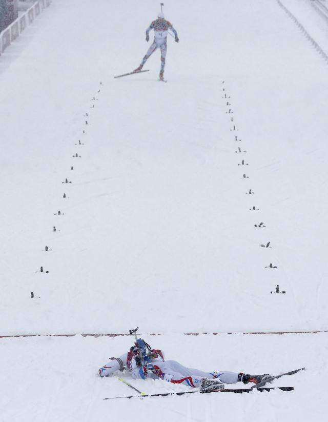 France's Martin Fourcade (bottom) lies on the ground after crossing the finish line as Czech Republic's Ondrej Moravec approaches during the men's biathlon 15km mass start event at the Sochi 2014 Winter Olympic Games in Rosa Khutor February 18, 2014. REUTERS/Stefan Wermuth (RUSSIA - Tags: SPORT BIATHLON OLYMPICS)