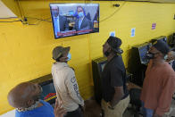 People gather inside a convenience store in the Houston neighborhood where George Floyd grew up, to listen to the verdict in the murder trial against former Minneapolis police Officer Derek Chauvin, Tuesday, April 20, 2021, in Houston. (AP Photo/David J. Phillip)