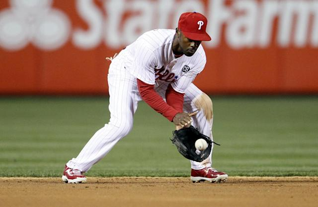 Philadelphia Phillies' Jimmy Rollins fields a ball hit by Miami Marlins' Marcell Ozuna during the third inning of a baseball game on Friday, April 11, 2014, in Philadelphia. (AP Photo/Tom Mihalek)