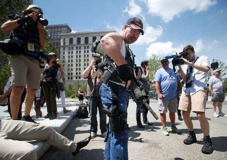Steve Thacker carrying a rifle and a handgun is surrounded by news media in a public square in Cleveland
